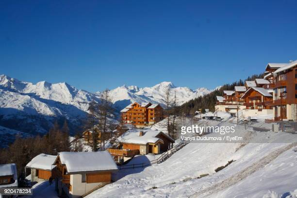 houses and snowcapped mountains against clear blue sky - savoie stock pictures, royalty-free photos & images