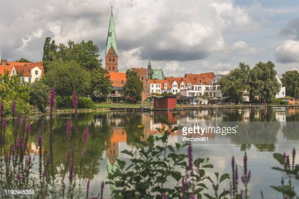 houses and st. aegidien-kirche by krhenteich lake against cloudy sky in lbeck, germany - kirche ストックフォトと画像