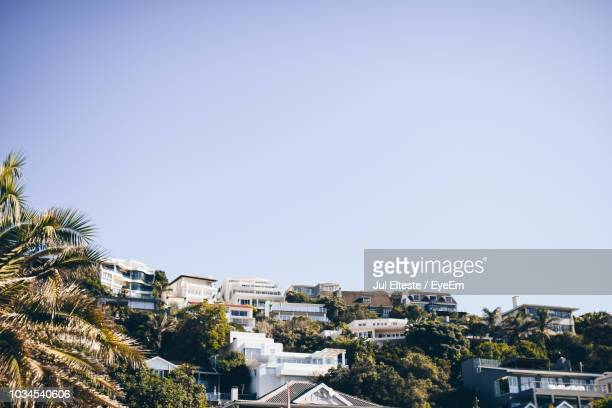 Houses And Trees Against Clear Blue Sky