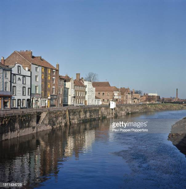 Houses and warehouses line one bank of a tidal section of the River Parrett on West Quay in the market town of Bridgwater in Somerset, England circa...