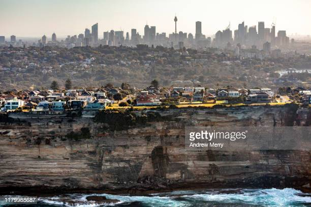 houses, apartment suburb at edge of rocky coastline with high sea cliffs and urban skyline cityscape, sydney, australia - sydney stock pictures, royalty-free photos & images