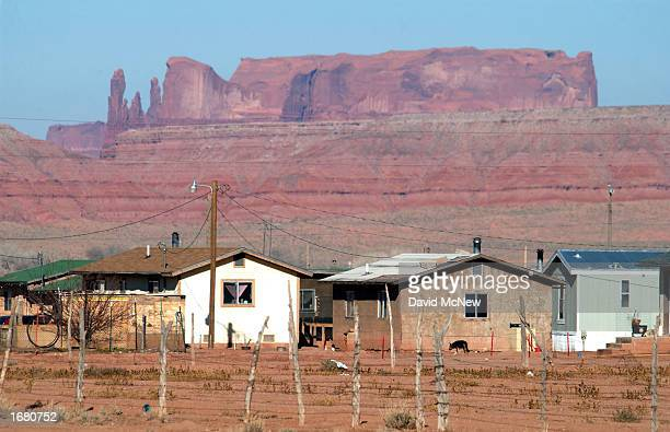 Houses are backed by sandstone cliffs north of Many Farms December 5 2002 on the Navajo Indian Reservation Arizona Tha Navajo Nation rejects the...