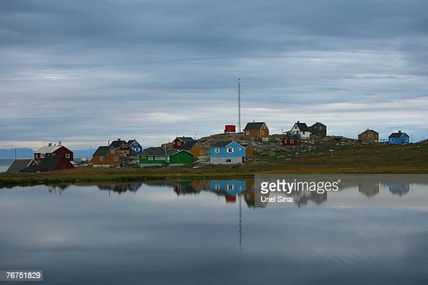 Houses are reflected in a lake August 26 2007 in Ilimanaq Greenland Arne Langa a 39yearold Inuit fisherman still remembers the last time the sea...