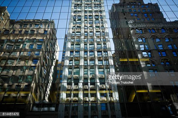 New York United States of America February 27 Houses are reflected in the glass facade of a skyscraper in Manhattan on February 27 2016 in New York...
