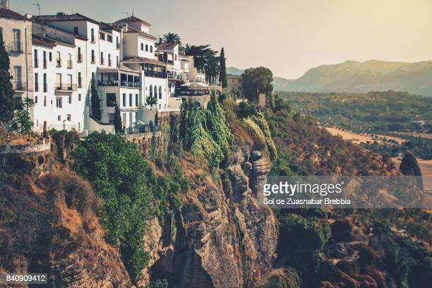 Houses at the edge of the cliff seen from the new bridge of Ronda, Spain.
