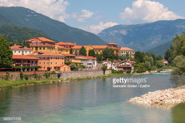 houses by buildings and mountains against sky - veneto stock pictures, royalty-free photos & images