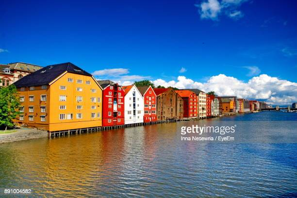 Houses By Lake Against Blue Sky