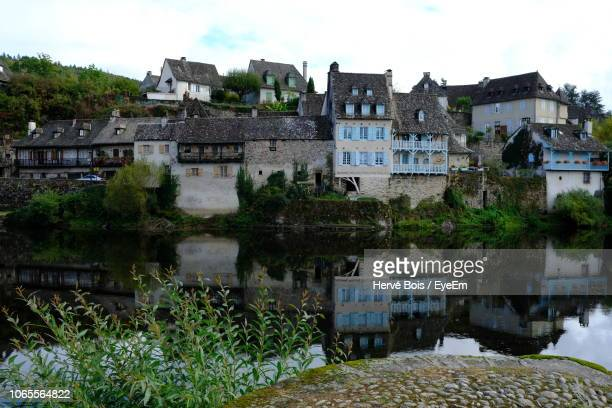 houses by lake against buildings in city against sky - correze stock pictures, royalty-free photos & images