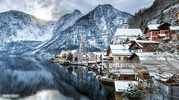 Houses By Lake Against Mountains At Hallstatt In Winter