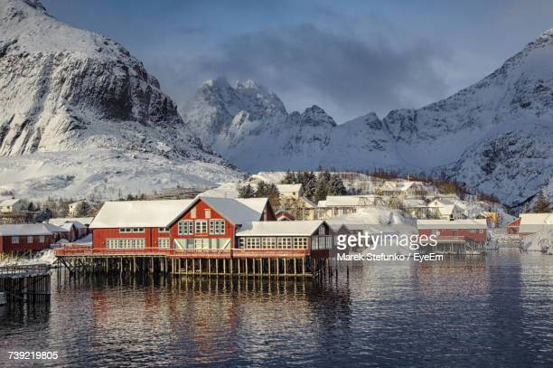 houses by lake against sky during winter - marek stefunko stock pictures, royalty-free photos & images