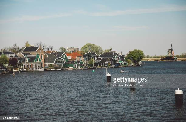 houses by lake against sky - bortes stockfoto's en -beelden
