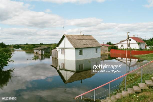 houses by lake against sky - extreme weather stock photos and pictures