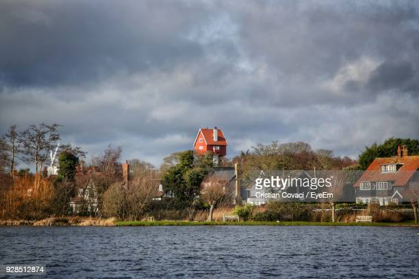 Houses By Lake Against Sky