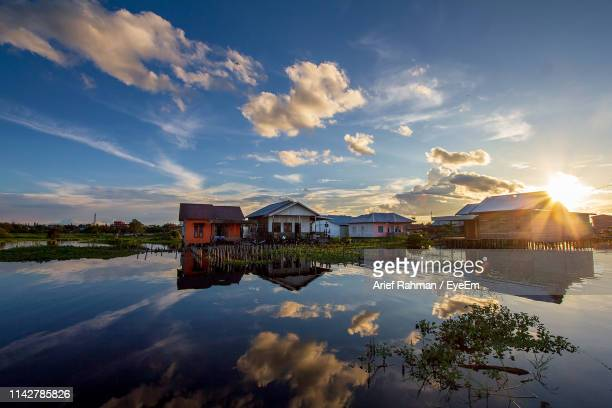 houses by lake and buildings against sky during sunset - central kalimantan stock pictures, royalty-free photos & images