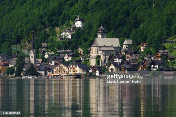 houses by lake and buildings in town - marek stefunko stock photos and pictures