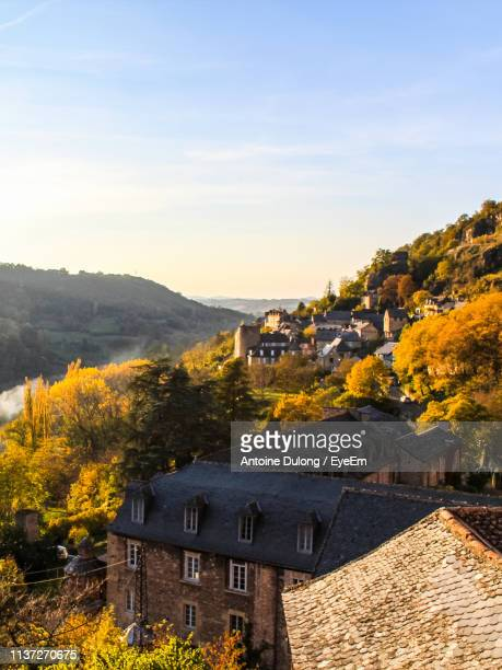 houses by mountain against sky during autumn - aveyron stock pictures, royalty-free photos & images