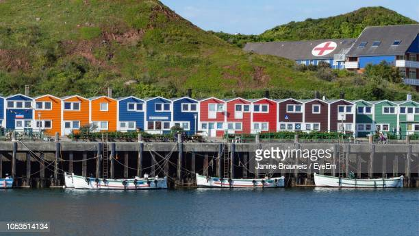 houses by river against buildings in city - helgoland stock pictures, royalty-free photos & images