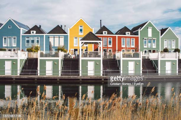 houses by river against buildings in city - bortes stock pictures, royalty-free photos & images