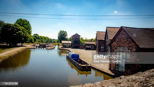 houses by river against sky - coventry stock pictures, royalty-free photos & images
