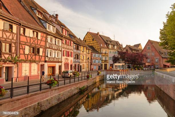 houses by river against sky - colmar stock photos and pictures