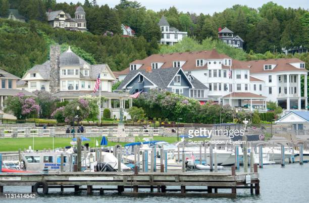 houses by river and buildings in town - mackinac island stock pictures, royalty-free photos & images