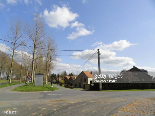 houses by road against sky in city - damme stock pictures, royalty-free photos & images