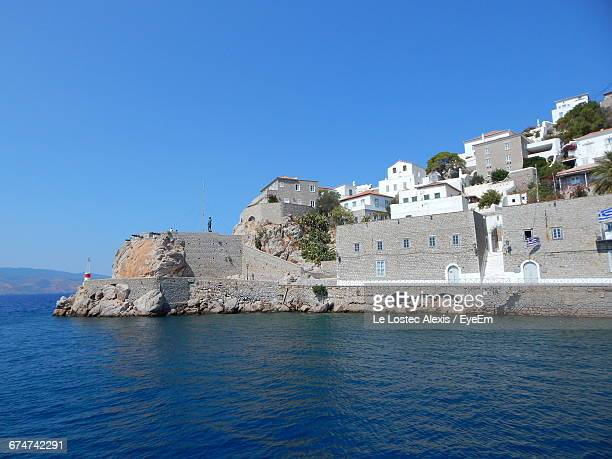 houses by sea against clear sky ay hydra - hydra stock photos and pictures