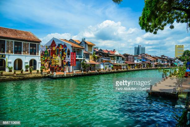 houses by sea against sky in city - melaka state stock pictures, royalty-free photos & images