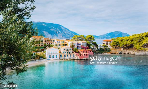 houses by sea in city against sky - greece stock pictures, royalty-free photos & images