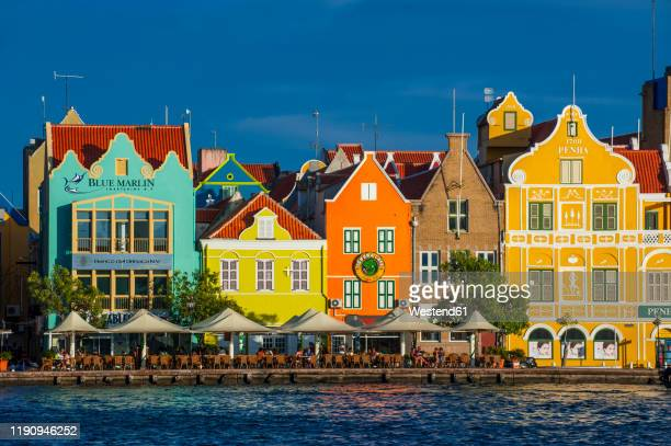 houses by sint annabaai against blue sky in willemstad city during sunny day, curaao - curaçao stockfoto's en -beelden