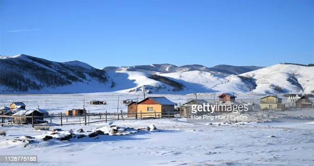 houses by snowcapped mountains against clear blue sky - モンゴル ストックフォトと画像