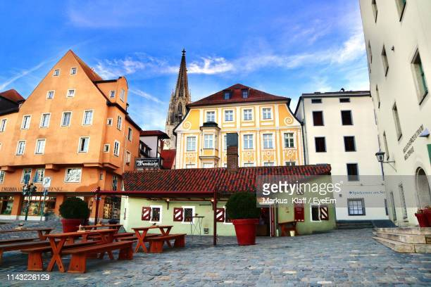 houses by street in town against sky - regensburg stock photos and pictures