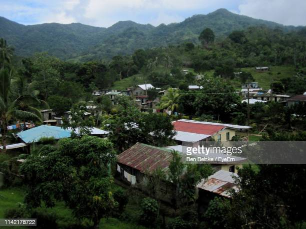 houses by trees and mountains against sky - fiji ストックフォトと画像