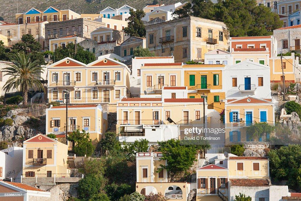 Houses clinging to hillside, Gialos, Symi, Greece : Foto stock
