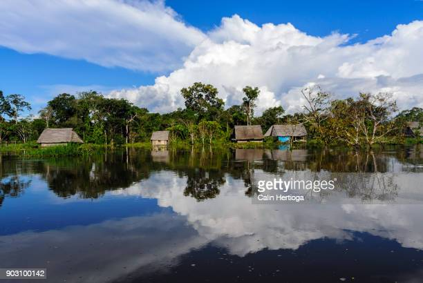 Houses, clouds and blue sky reflected in the Amazon river