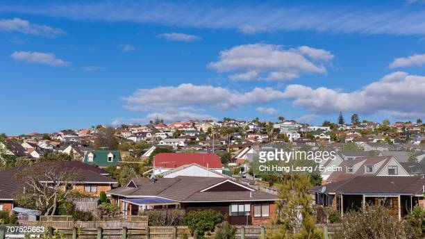 Houses In City Against Cloudy Sky