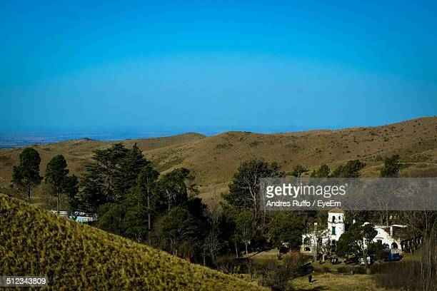 houses in middle of mountains against clear blue sky - andres ruffo stock-fotos und bilder