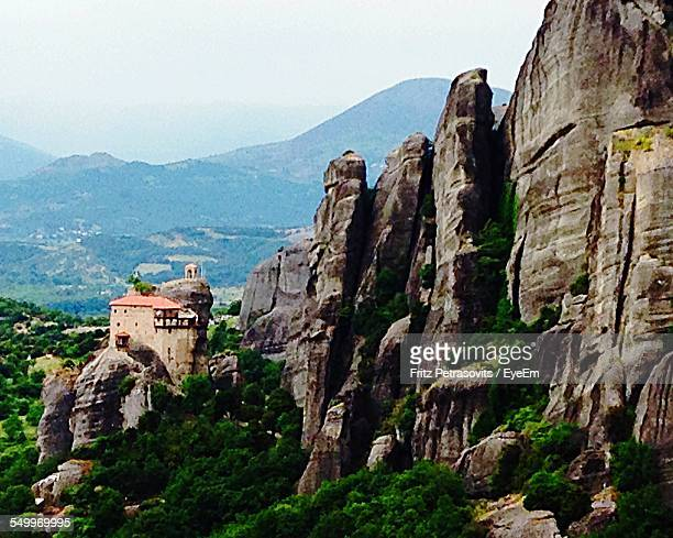 Houses In Rocky Mountains Against Sky At Meteora