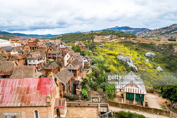 houses in town by mountains against sky - antananarivo stock photos and pictures