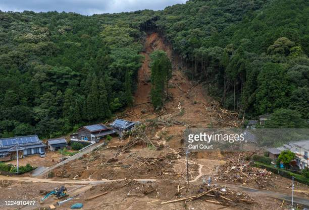 Houses lie submerged in mud after a landslide caused by torrential rain, on July 6, 2020 in Ashikita, Japan. Around 37 people are believed to be dead...