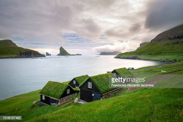 houses near the small village of bøur, with drangarnir and tindhólmur on background. faroe islands - islas faroe fotografías e imágenes de stock