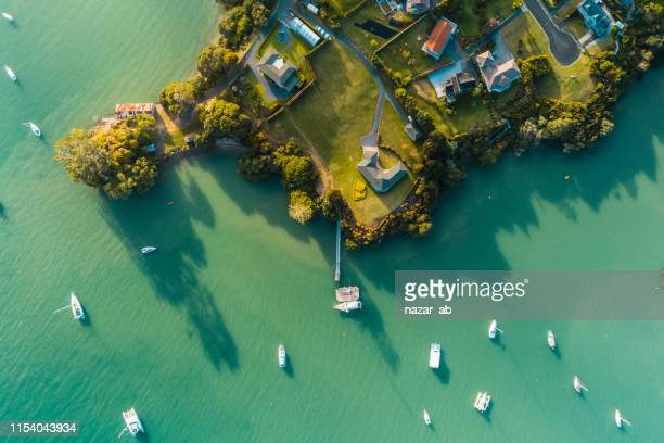 houses next to beach and boat. - northland new zealand stock pictures, royalty-free photos & images
