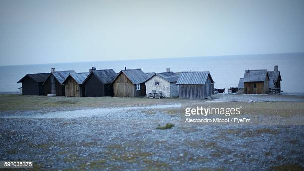 houses on beach against clear sky at dusk - alessandro miccoli stockfoto's en -beelden