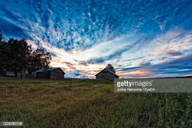 houses on field against sky - heinovirta stock photos and pictures