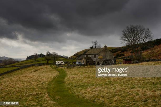 houses on field against sky - storm stock pictures, royalty-free photos & images
