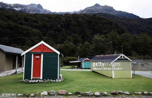 houses on field by green mountain - southland new zealand stock pictures, royalty-free photos & images