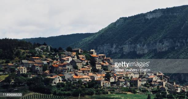 houses on mountain against sky - aveyron stock pictures, royalty-free photos & images