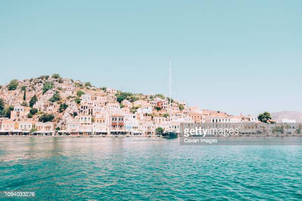 houses on mountain by sea against clear blue sky during sunny day - symi foto e immagini stock