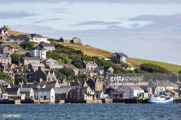 houses on mountain by sea against sky - town stock pictures, royalty-free photos & images