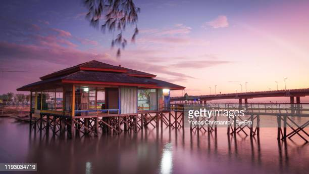 houses on pier by sea against sky during sunset - surabaya stock pictures, royalty-free photos & images